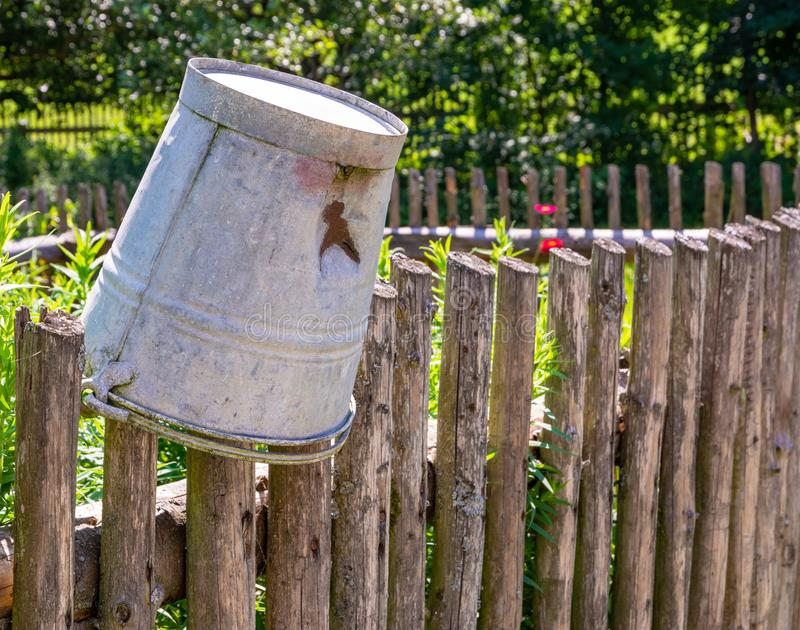 Vintage tin bucket on the fence of a vegetable garden. Vintage tin bucket on the wooden fence of a vegetable garden stock photography