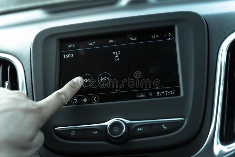 Filtered tone male hand changing the radio station on car LCD infotainment screen stock photo