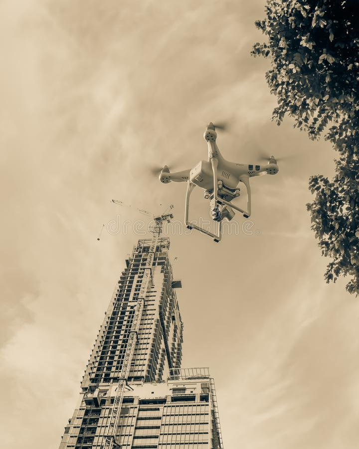 Filtered tone image of drone on construction site working crane royalty free stock image