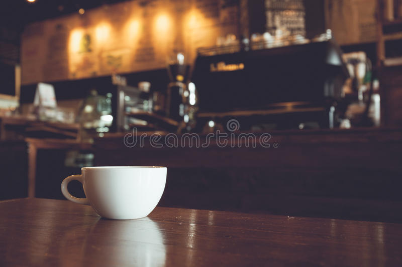 Vintage tone of white cup of coffee on wooden bar in Coffee shop royalty free stock photo
