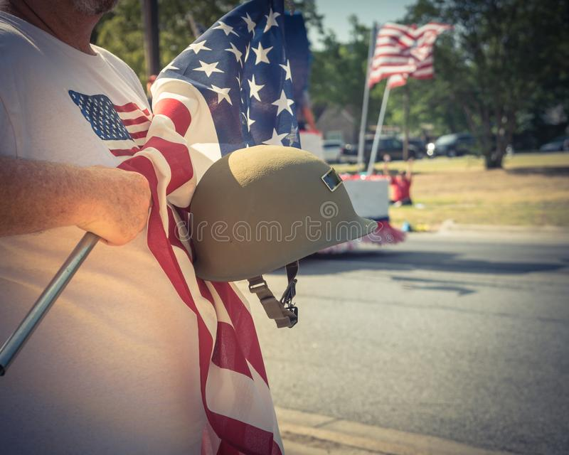 Vintage tone veteran with US flag and WWI helmet on parade. Vintage tone a white veteran proudly holding military WWI helmet M1 helmet and US flag. July 4th or stock photo
