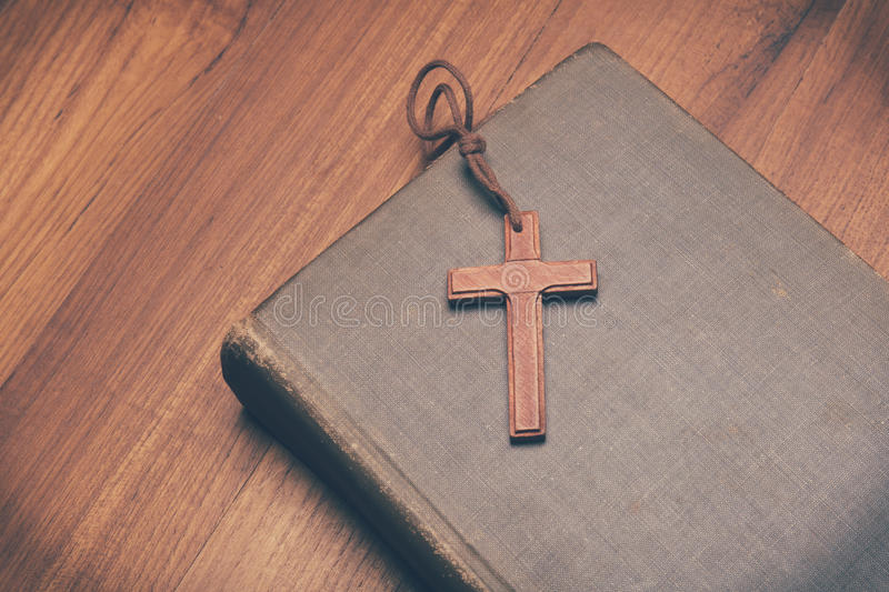 Vintage tone of wooden Christian cross necklace on holy Bible royalty free stock images