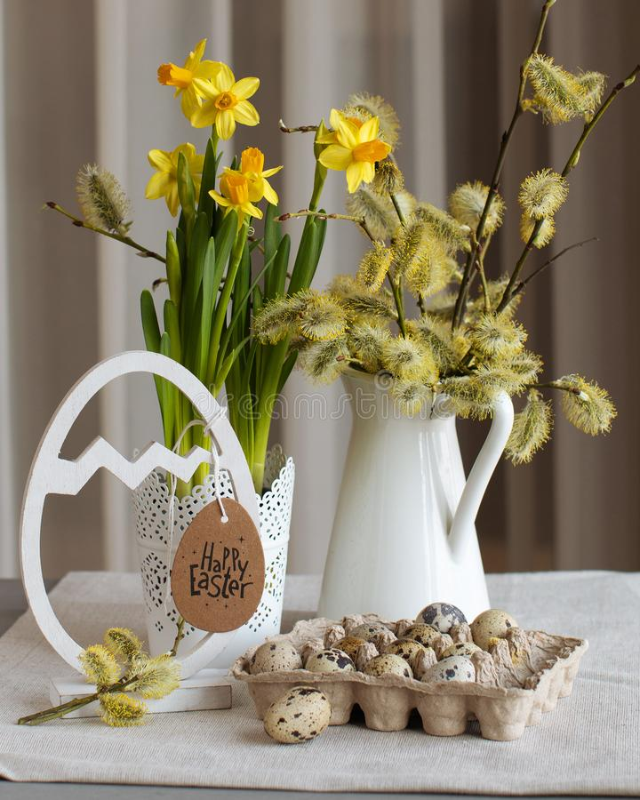 Vintage toned Easter still life with alder branches, daffodil bulbs and quail eggs. Vintage style Easter still life with alder branches in a white metal jar royalty free stock image