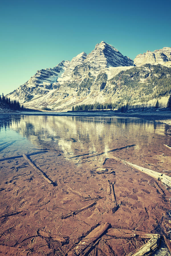 Vintage toned Maroon Bells reflected in frozen lake, Colorado, U. SA royalty free stock photography