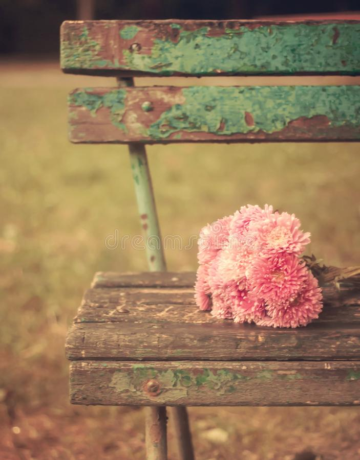 Vintage toned picture of pink flowers bouquet on a wooden old bench stock photo