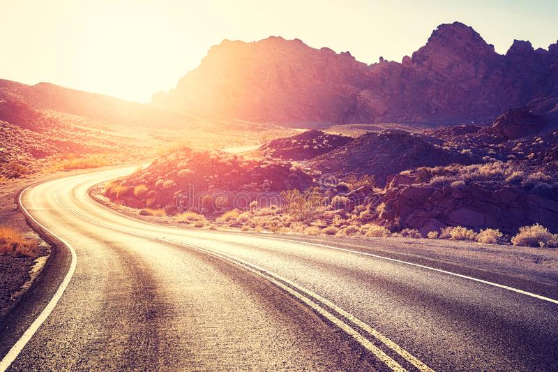 Vintage toned scenic desert road at sunset, USA. stock photos