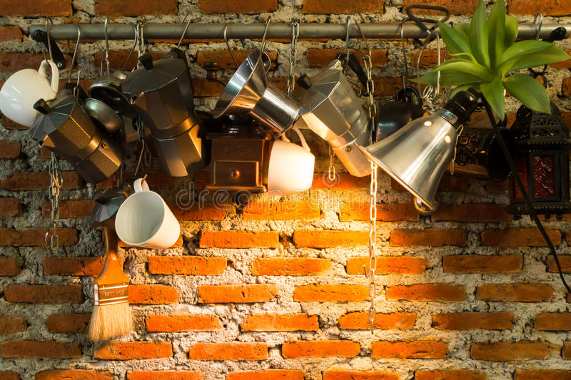 Vintage tones interior and decorations of a coffee shop, cafe. Vintage brown brick wall and hanging with making coffee materials. Space on middle with light stock photos