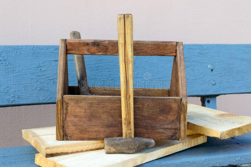 Vintage Toolbox with tools. Old wooden box with building tools, boards for repair on a wooden bench. royalty free stock photography