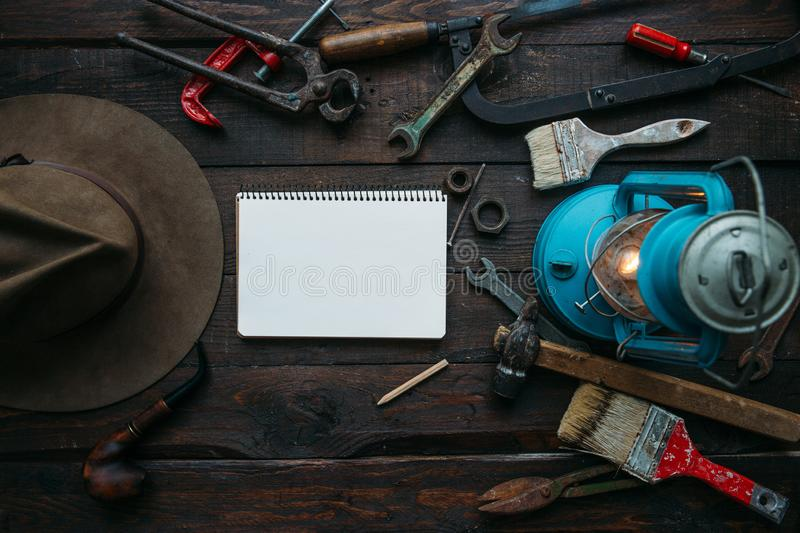 Vintage tools set, hat, gas lamp on dark brown wooden background. Father's day concept with empty space for copy, text, lettering royalty free stock photography