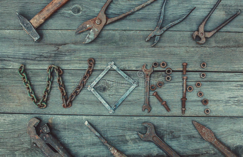 Vintage tools on a wooden surface. On the old,wooden,cracked,the working surface are vintage,used,rusty,discolored,metal,dirty tools for repair royalty free stock images