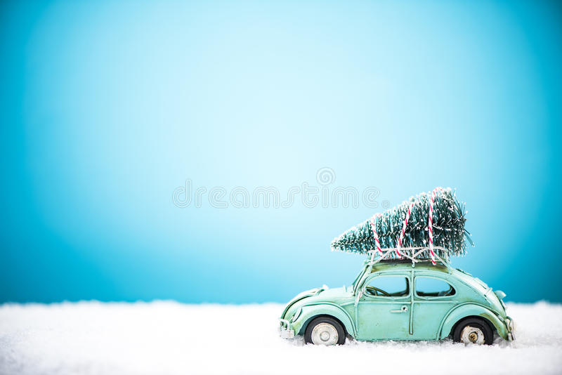 Vintage toy car carry Christmas tree in snow stock photos