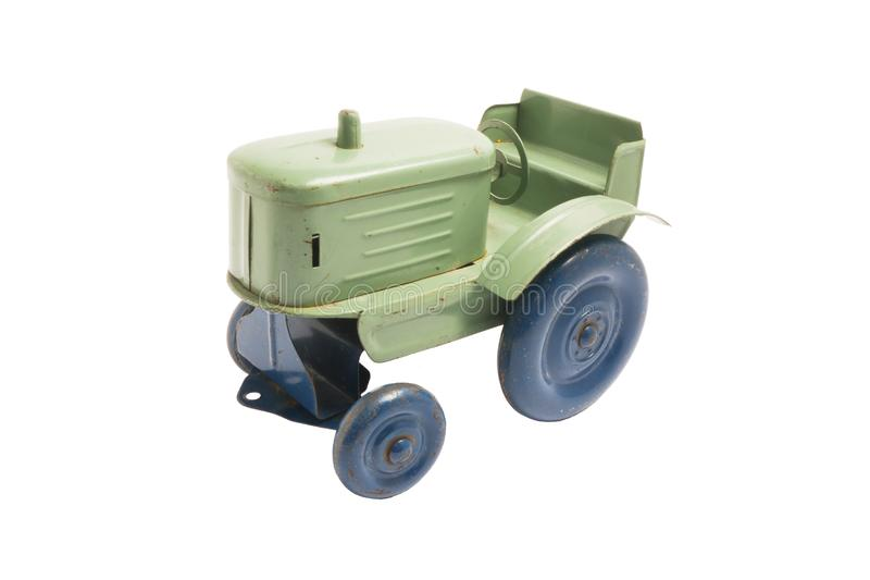 Vintage toy green metal tractor with blue wheels on white isolated background royalty free stock photos