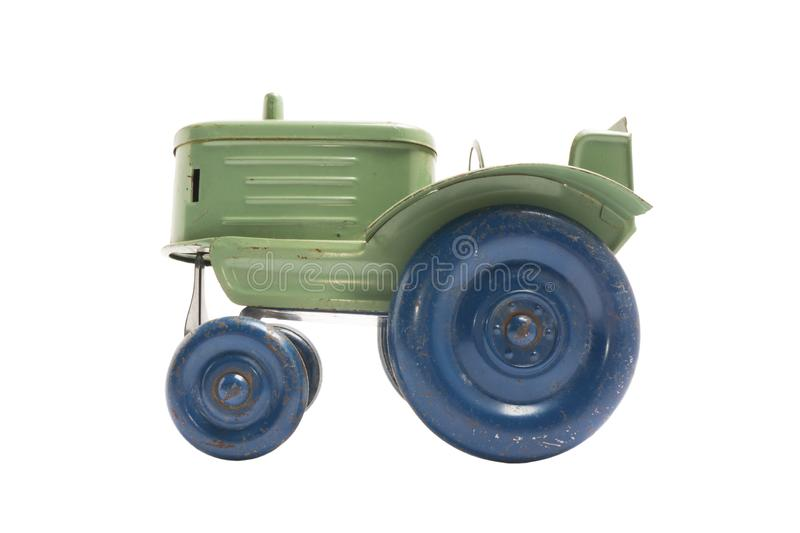 Vintage toy green metal tractor with blue wheels on white isolated background royalty free stock image