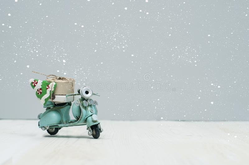 Vintage toy motorbike with christmas gifts and tree. On grey background royalty free stock photo