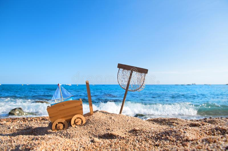 Vintage toys at the beach. Fishing net and vintage toys in sand at the beach stock images