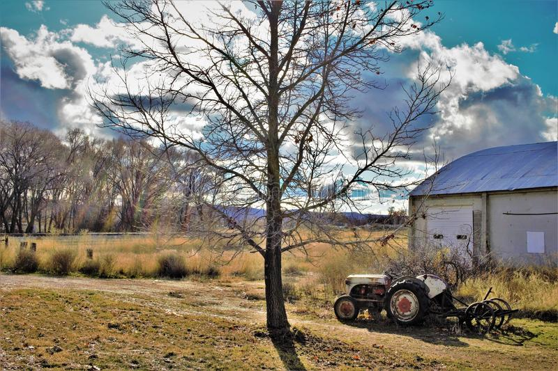 Vintage tractor and implement in front of barn. Under a tree. clouds and blue sky back ground stock photo