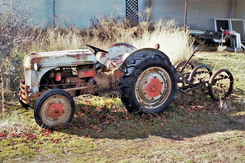 Vintage tractor and implement in front of barn. Under a tree. clouds and blue sky back ground stock images