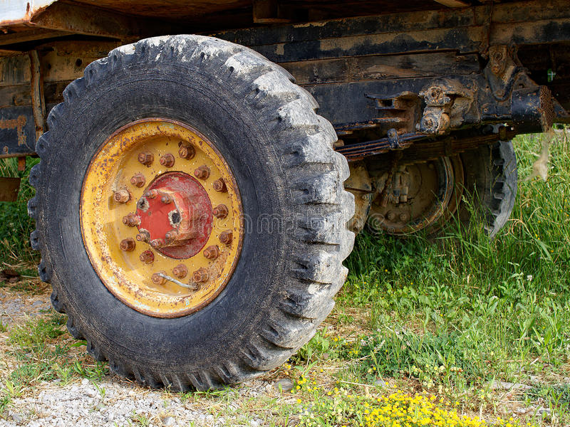 Vintage Tractor Trailer Wheel and Suspension. Detail of a very old yellow rusted vintage tractor trailer wheel and leaf spring suspension, including rigid axel royalty free stock images