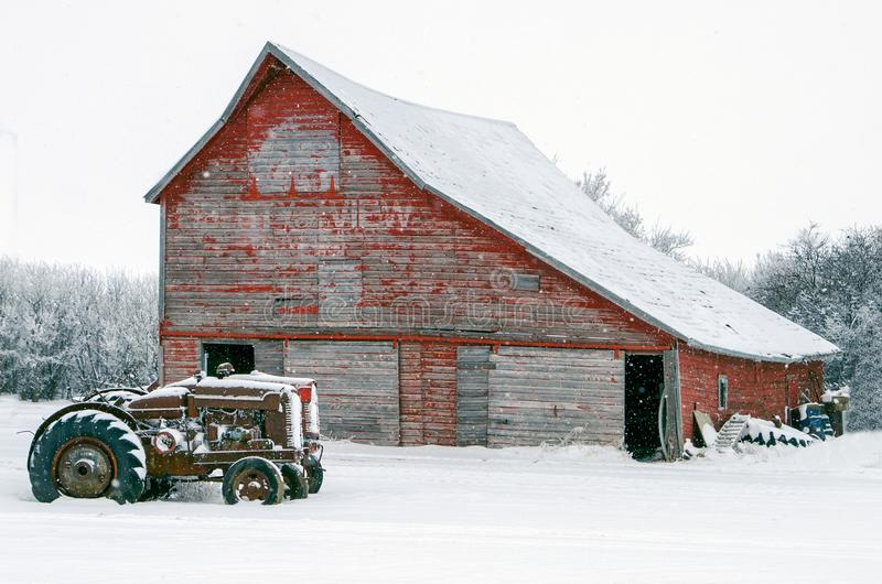Vintage tractors in front of an old red barn in snow stock photos
