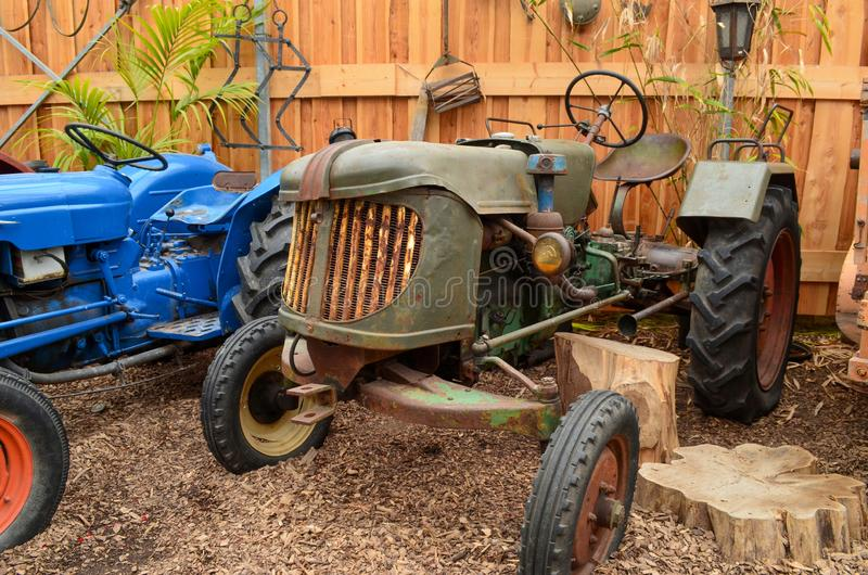 Vintage tractors parked in a barn. With a wooden fence in the background royalty free stock image