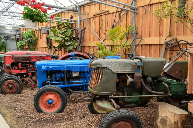 Vintage tractors parked in a barn. With a wooden fence in the background stock images