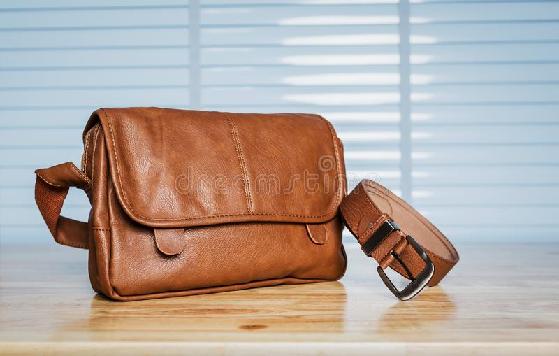 Vintage travelling for men`s accessories, brown bag and belt put. Vintage travelling for men`s accessories, a brown bag and belt put on modern wooden desk table stock photography