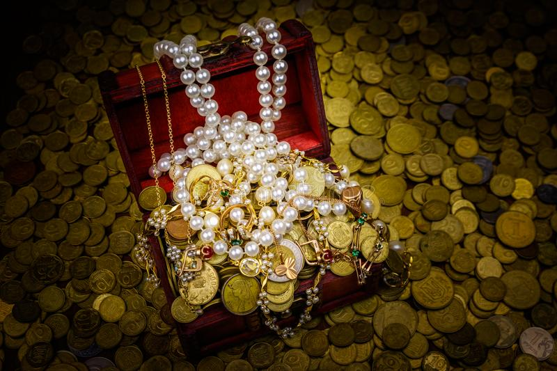 Vintage treasure chest full of gold coins and jewelry on a background of golden coins. Vintage treasure chest full of gold coins and jewelry on background of royalty free stock photo