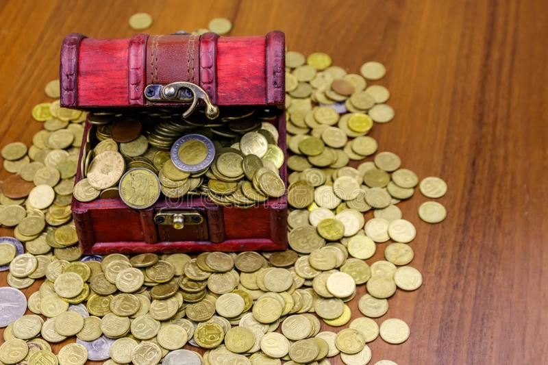 Vintage treasure chest full of golden coins on wooden background. Vintage treasure chest full of golden coins on a wooden background stock photos