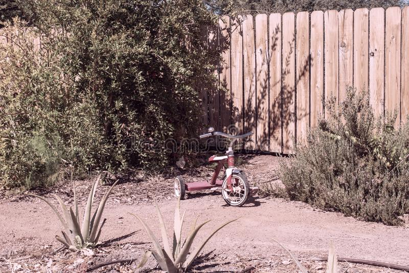 Vintage tricycle sitting in a yard. Old tricycle sitting in a desert landscape back yard with wooden fence stock photo