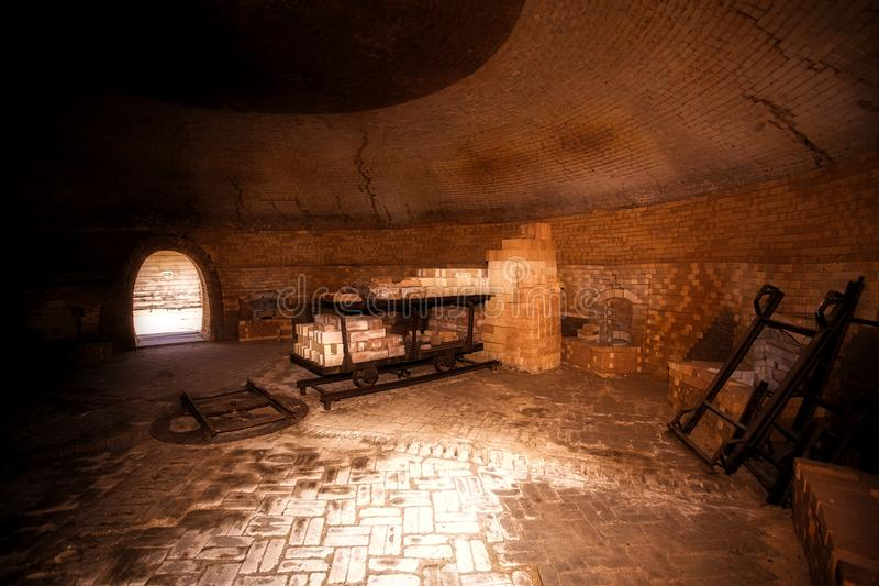 Vintage trolley loaded with bricks in a kiln. The interior of a large circular abandoned old kiln with stack of bricks along outer edge stock image