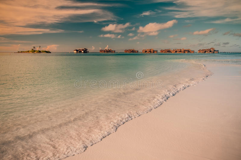 Vintage Tropical beach background. Crystal clear water and luxury water bungalows. Tropical tranquil background concept stock photos