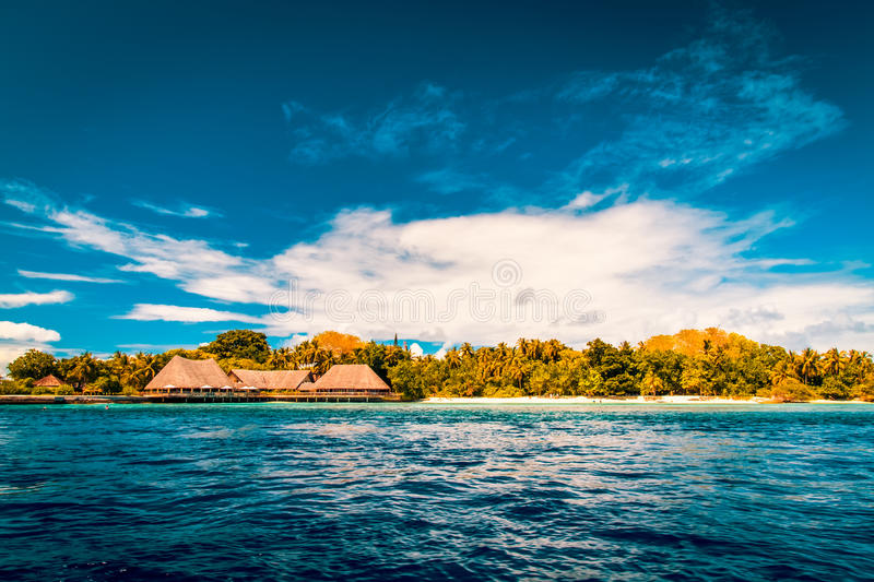 Vintage Tropical beach background. Crystal clear water and luxury water bungalows. Tropical tranquil background concept royalty free stock image