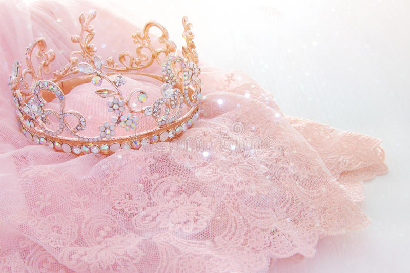 Vintage tulle pink chiffon dress and diamond tiara on wooden white table. Wedding and girl& x27;s party concept royalty free stock photography