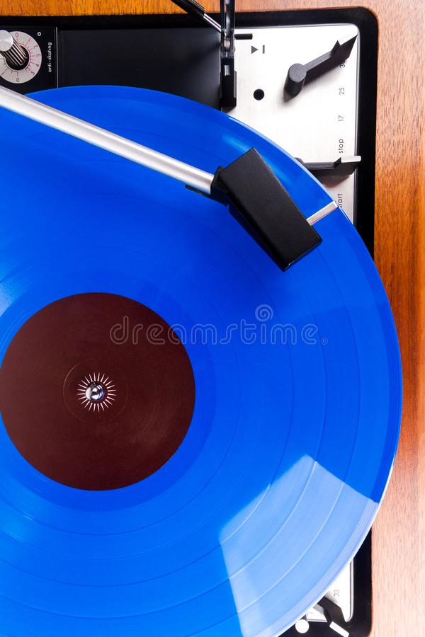 Vintage turntable with a blue vinyl. Close up of vintage turntable with a blue vinyl. Wooden plinth. Retro audio equipment royalty free stock photo