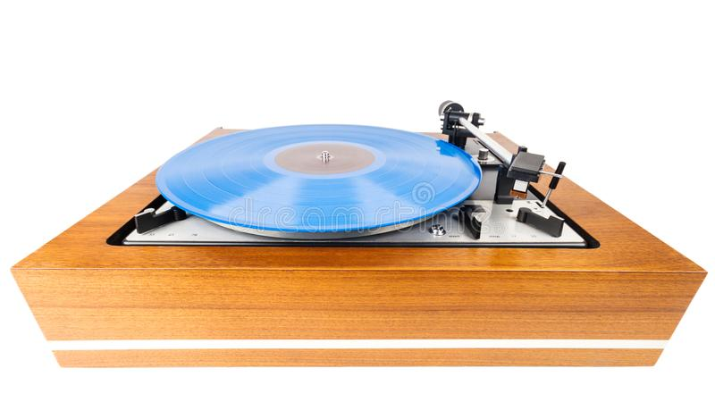 Vintage turntable with a blue vinyl isolated on white. Wooden plinth. Retro audio equipment stock photo