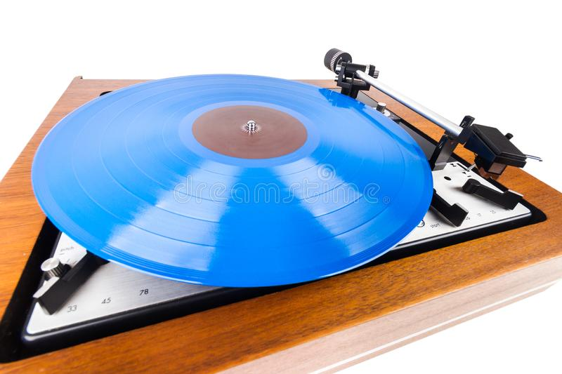 Vintage turntable with a blue vinyl isolated on white. Wooden plinth. Retro audio equipment royalty free stock image