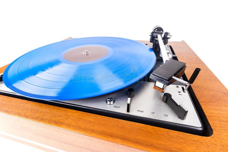 Vintage turntable with a blue vinyl isolated on white. Wooden plinth. Retro audio equipment stock image
