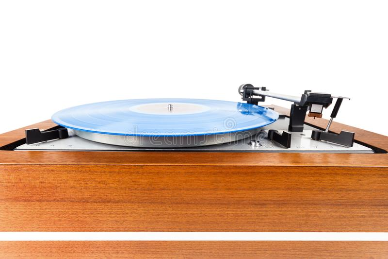 Vintage turntable with a blue vinyl isolated on white. Wooden plinth. Retro audio equipment royalty free stock photo