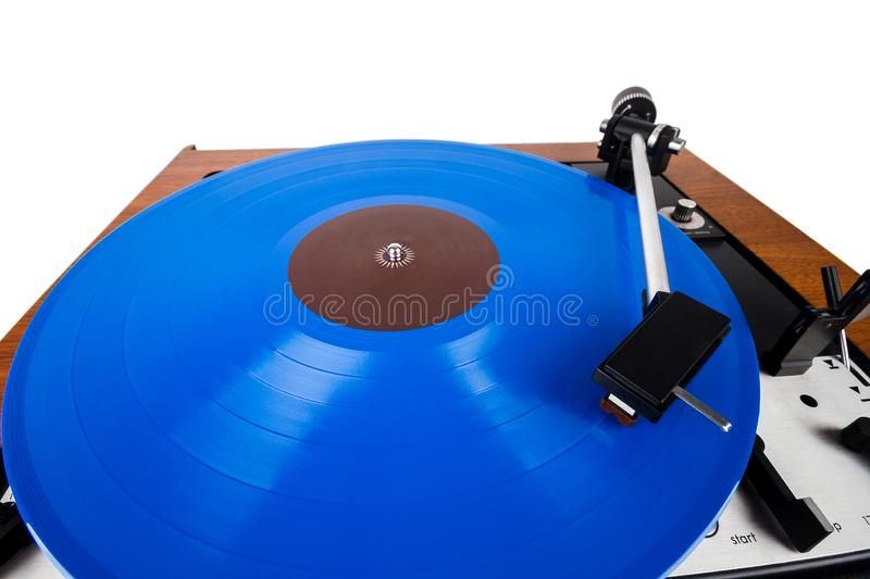 Vintage turntable with a blue vinyl  on white. Wooden plinth. Retro audio equipment stock photography