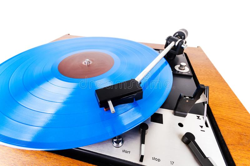 Vintage turntable with a blue vinyl  on white. Wooden plinth. Retro audio equipment stock photos