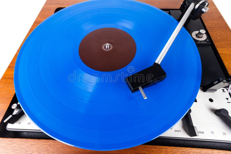 Vintage turntable with a blue vinyl isolated on white. Wooden plinth. Retro audio equipment stock photos