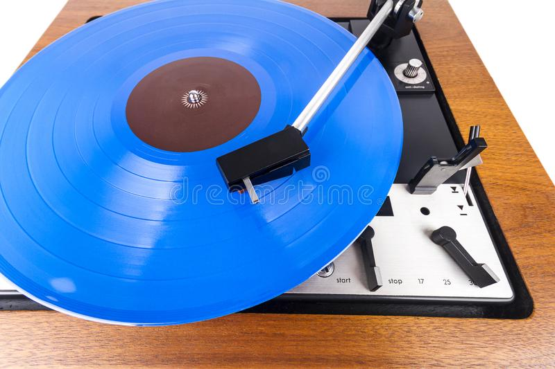 Vintage turntable with a blue vinyl isolated on white. Wooden plinth. Retro audio equipment stock photography