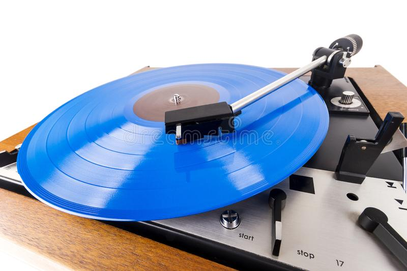 Vintage turntable with a blue vinyl isolated on white. Wooden plinth. Retro audio equipment royalty free stock photography