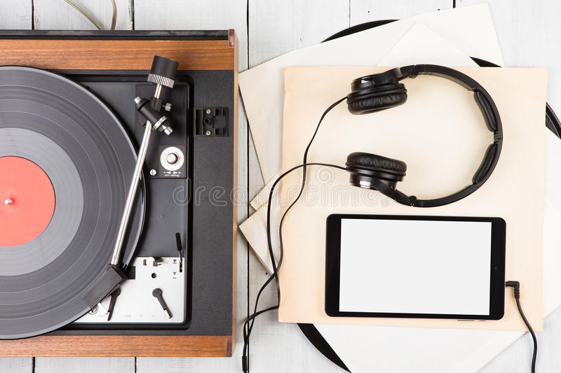 Vintage turntable, smartphone and headphones. On the wooden background royalty free stock photography