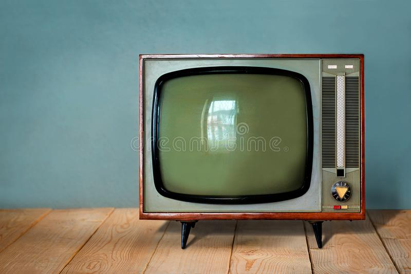 Vintage TV set on wooden table against old blue wall stock photos