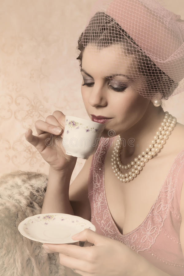 Vintage twenties woman. Attractive vintage 1920s lady with flapper dress and matching hat drinking tea stock photo