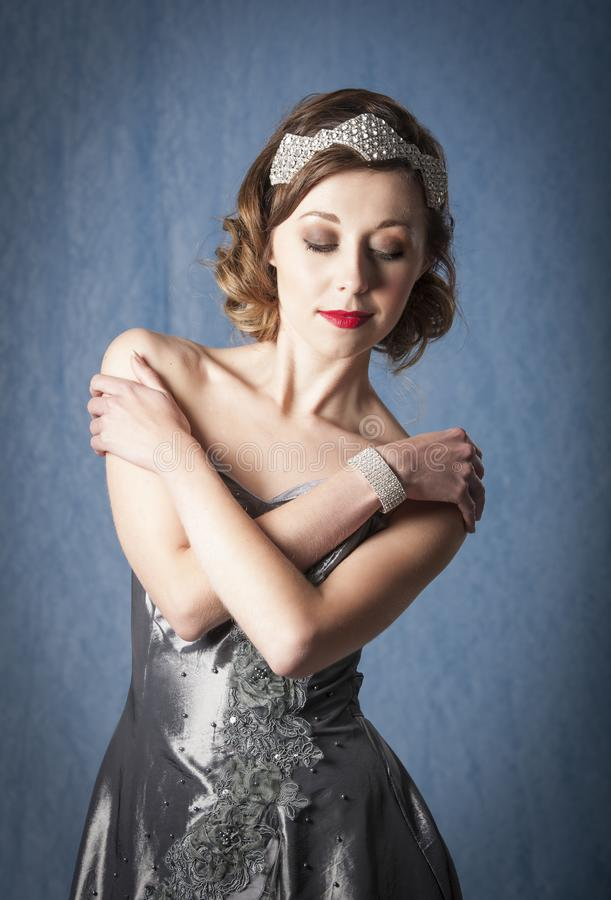 Vintage twenties woman wearing diamond hair accessory and bracelet, posing in front of a blue background in a grey evening dress. Color portrait of a vintage royalty free stock images