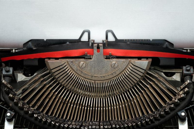 Vintage typewriter black and red ribbon and typebars. Close vintage typewriter black and red ribbon and typebars ready to type on a blank textured sheet stock images