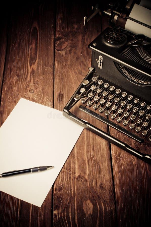 Vintage typewriter and a blank sheet of paper. Retouching retro stock photos