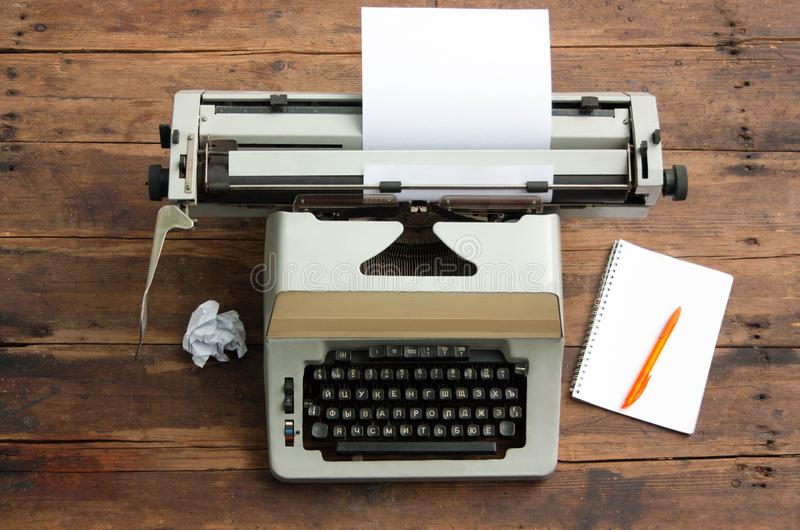 Vintage typewriter with the Cyrillic alphabet and a sheet of paper on an old table, a notebook and a pen. Vintage typewriter with the Cyrillic alphabet and a royalty free stock photo